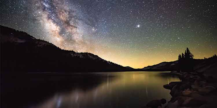 Night hiking scene of mountains and a lake under the Milky Way.