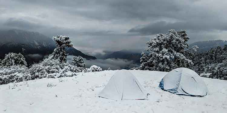 A snowy scene of two four-season tents set up at a camp in the mountains.