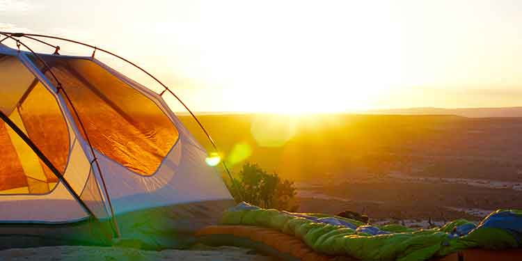 A three-season tent set up on a ridge basking in a beautiful sunrise.