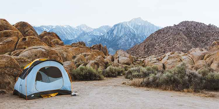 A three-season tent set up in a rocky dessert area with mountains in the background.