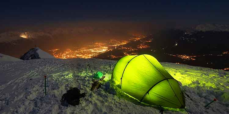 A four-season tent set up at a camp above the tree line in the snow overlooking a beautiful view of a city lit up at night.