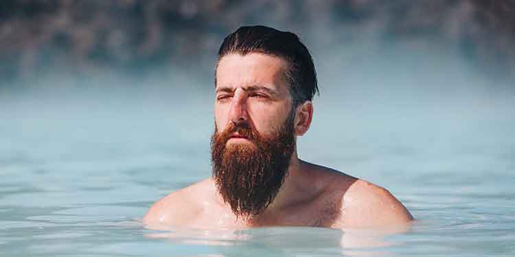 A man with a long beard practicing self care outdoor in a salt water pool.