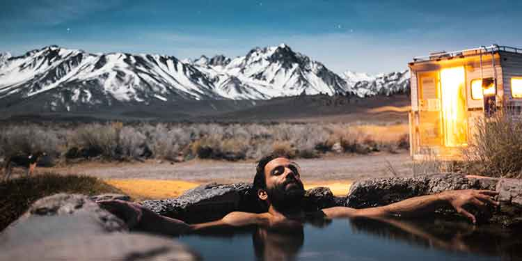A man with a beard relaxing in a spring feed pool of water outdoor under the stars at night.