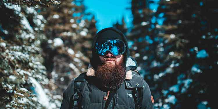 A bearded man in ski goggles on an outdoor adventure.