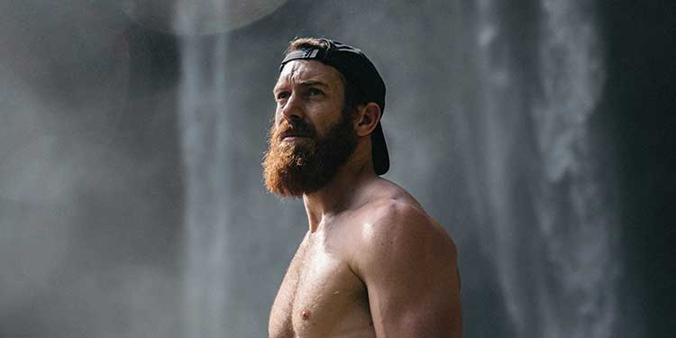 A muscular outdoorsy man with a longer beard stands shirtless in front of a waterfall.