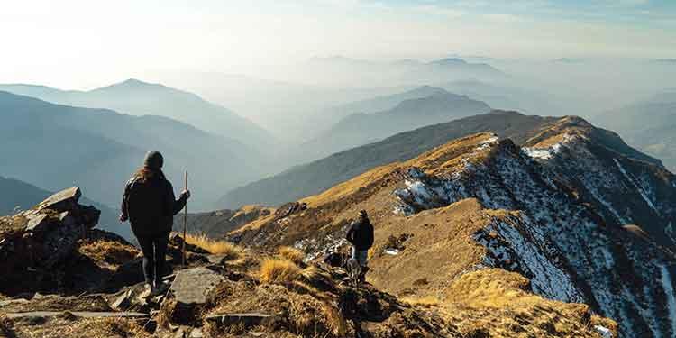 Two hikers make their way along a treacherous mountain ridge.