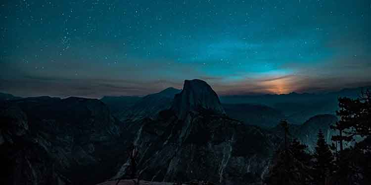 Dark mountain scene as the last glimmer of light disappears over the horizon.