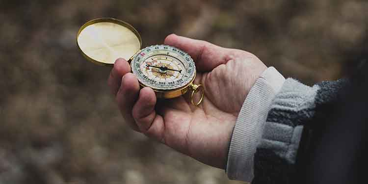 A lost hiker using a compass to find his direction.