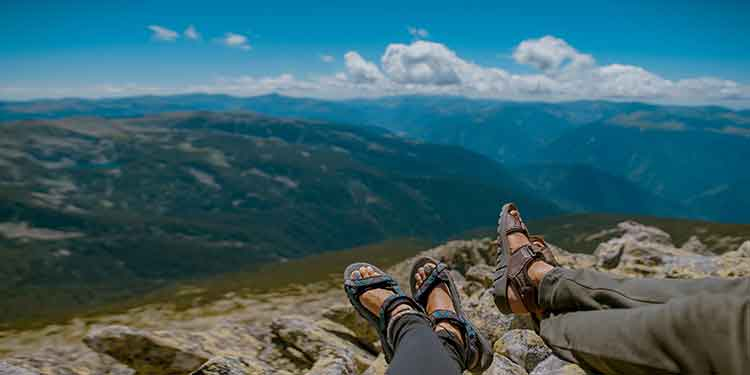 Two hikers taking a break and enjoying a mountain view. Both hikers are wearing sandals, inappropriate footwear for the hike.