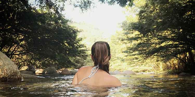 A woman in a bikini swims in a creek with giardia risks contracting giardiasis.