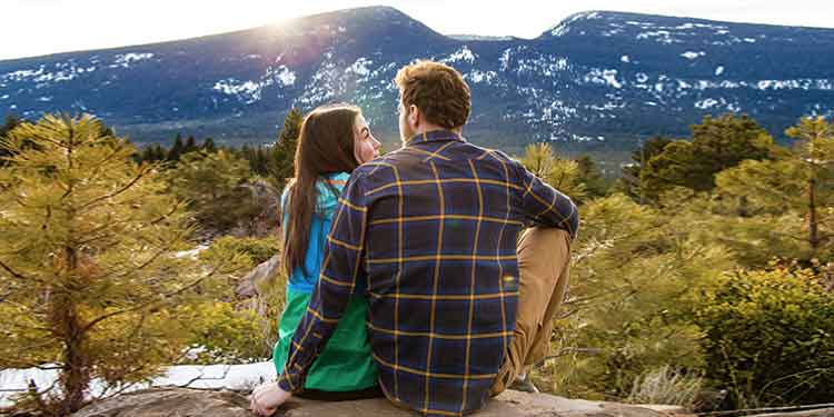 An attractive couple on a hiking date take a break to sit close to each other and enjoy the views on their outdoor adventure.