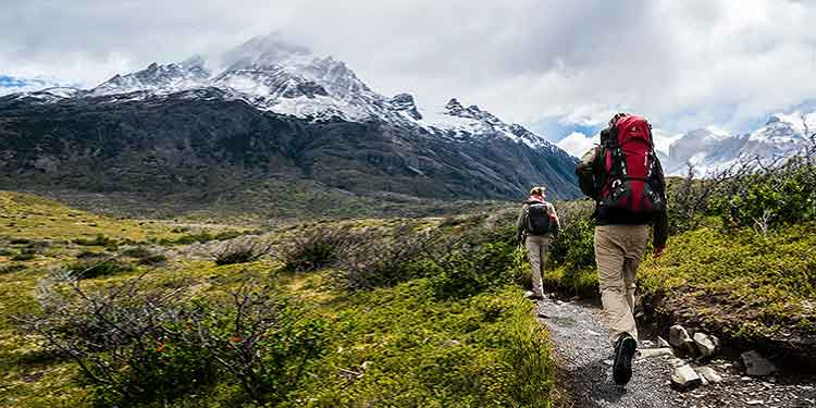 A male and female couple hiking in a valley toward a snow capped mountain.