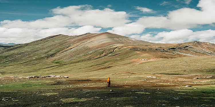 A trekker on a journey in a barren valley at the foot of a mountain range.