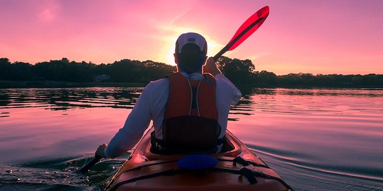 A man with high-angle paddling style kayaking toward the shoreline at sunset.