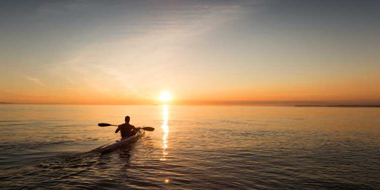 A man in a touring kayak with low-angle paddling style kayaking on still ocean water into the sunset.