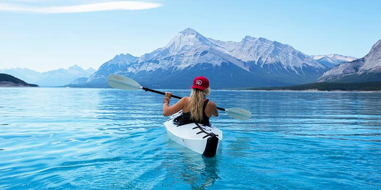 Woman kayaking on a lake with mountains miles in the distance.