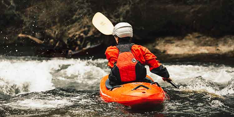 A kayaker on a fast-flowing river approaching rapids.