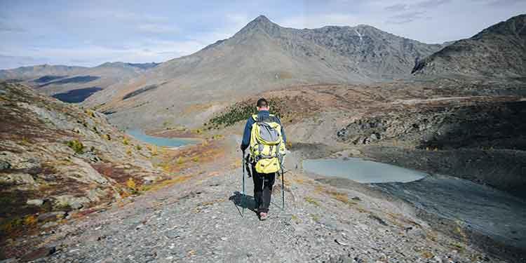 A backpacker braces himself with trekking poles to protect his knees while hiking down a rocky mountain path.