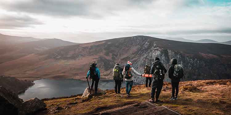 A hiking group of buddies on a mountain trail taking in the view of a lake down below.