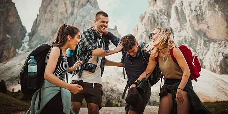 A close group of hiking friends playfully engaging with each other.