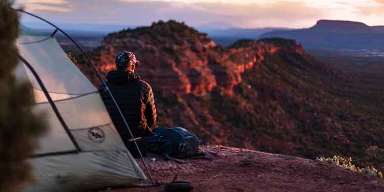 Camper sitting in front of his tent watching the sunset over a canyon.