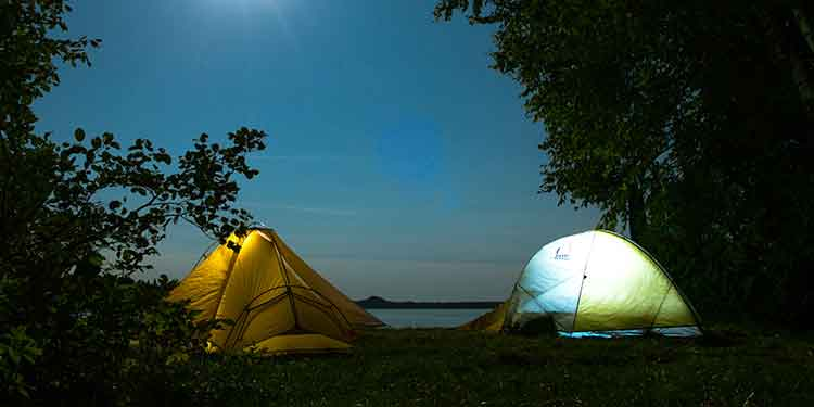 Two tents near a lake at night. Tents are zipped up to keep insects out.