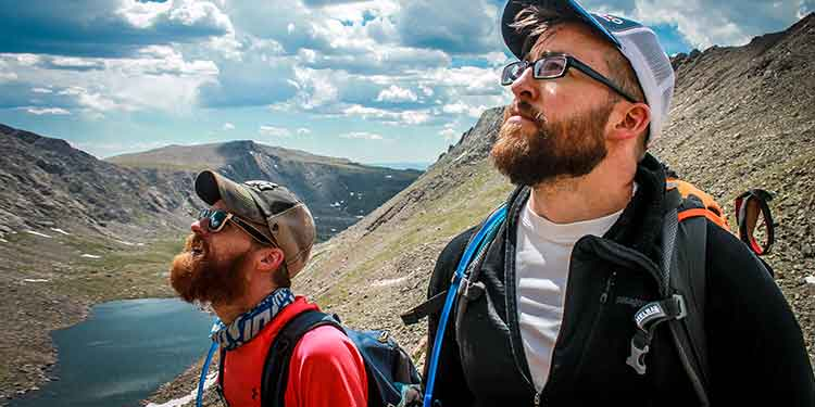 Two hikers use hydration packs filled with water to prevent dehydration on their hike.