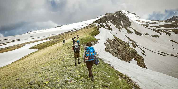 A group of hikers in risk of dehydration hike along a snowy mountain ridge.