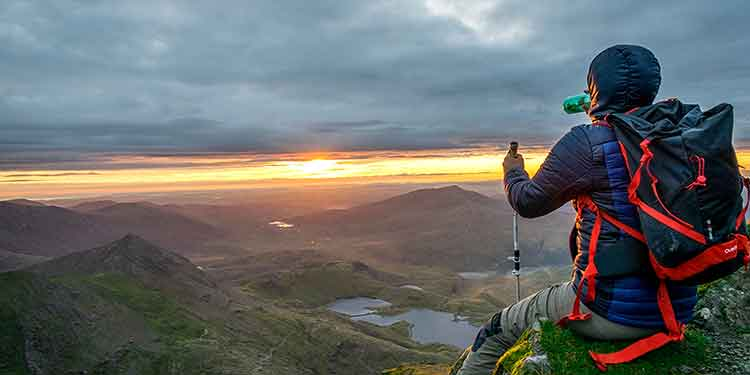 A hiker stops to hydrate with water while watching a beautiful sunset in the mountains.