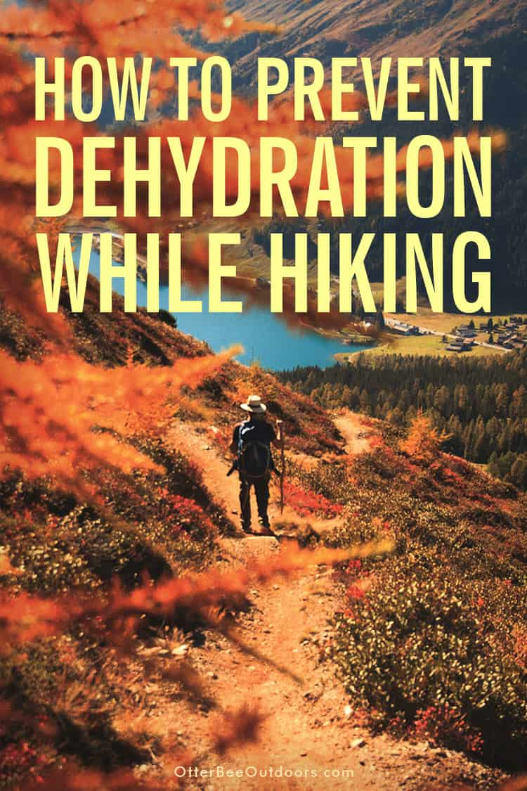 A man hiking down a mountain trail toward a lake in beautiful Fall scenery. Text says... How to Prevent Dehydration While Hiking.