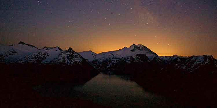Mountains silhouetted in the night sky with a lake in the foreground.