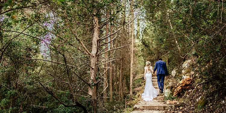 A bride in a wedding gown walks beside her groom up a trail in the woods.