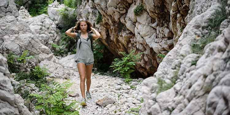 A beautiful woman hiking alone along a rocky trail