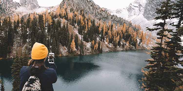 A woman on a solo hike stops to take a picture of a beautiful lake high up in the mountains.