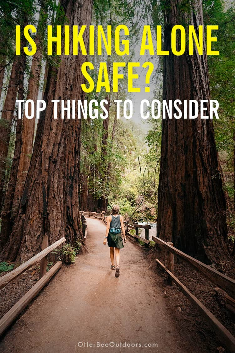 A young woman hiking alone on a park trail. Text asks... Is Hiking Alone Safe? Top things to Consider.