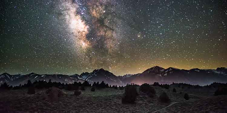 Stars and Milky Way in a night sky over a mountain chain and hiking trail.