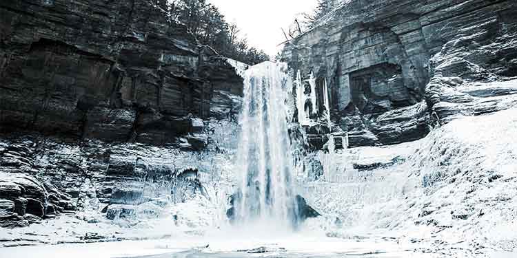 A frozen waterfall increases dangers for hikers including the risk of falling on the icy trails around it.