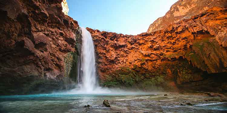 A beautiful waterfall coming off orangey colored mountains fill a pool along a hiking trail