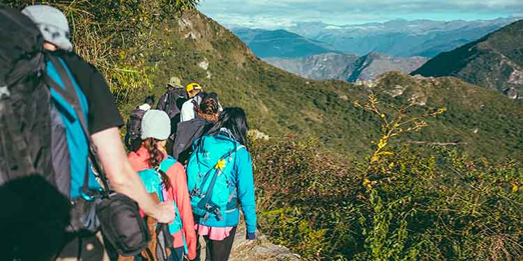 A group of hikers hiking along a mountain trail.