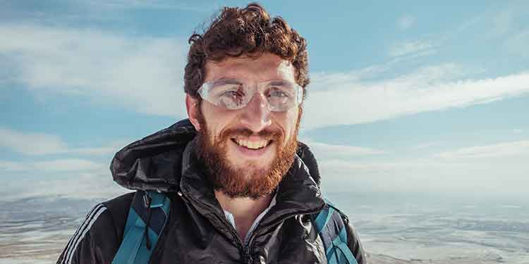 Happy male hiker smiling as he hikes at a higher altitude.
