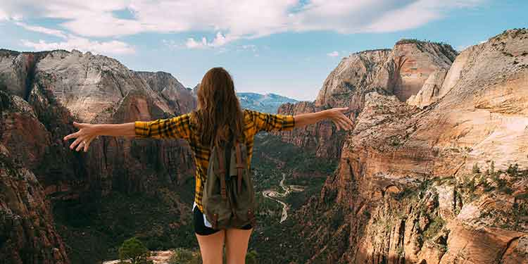 Female hiker standing with arms outstretched taking in the wondrous view of a deep canyon with river below.