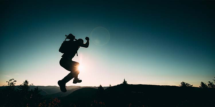 Physically energetic male hiker jumping.