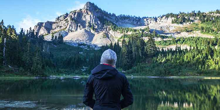 Female hiker taking time to enjoy a mountain view with lake below.