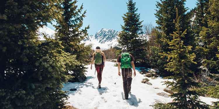 A couple enjoying a mountain trail on a hiking date.