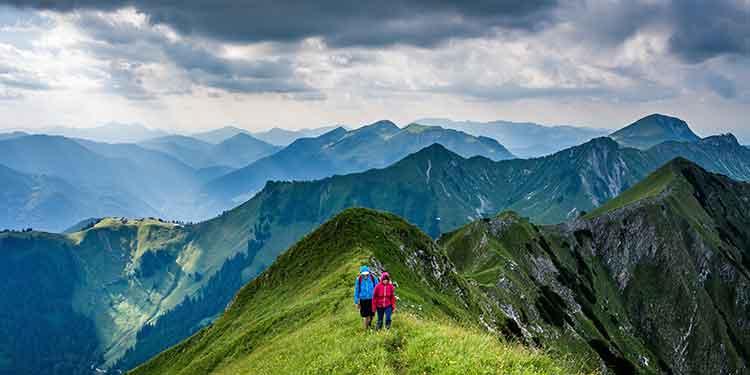 A couple on a hiking along a mountain ridge trail.