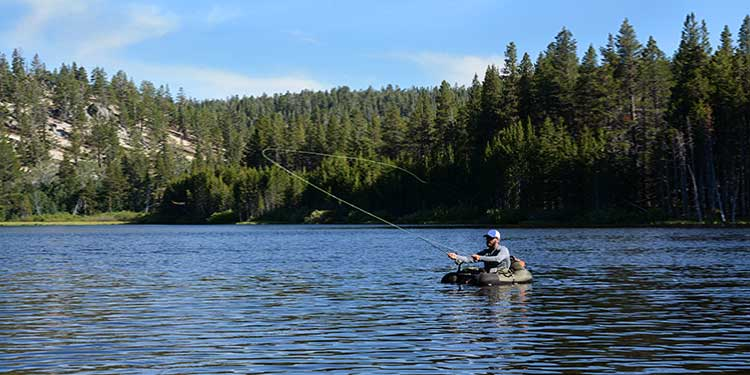 A man fly fishing from a fishing float tube in open water on a lake.