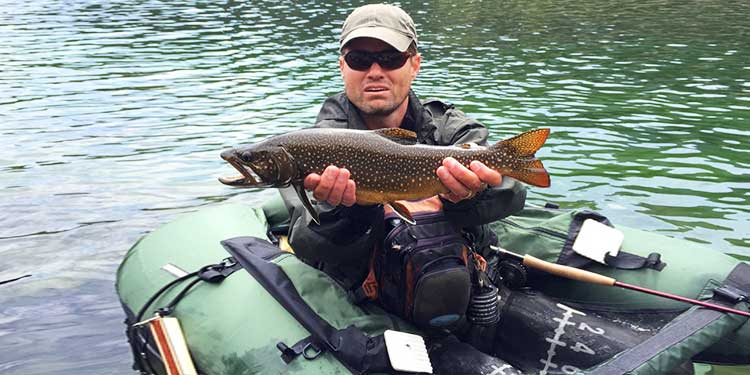 Man fly fishing from a pontoon or fishing float tube with his catch, large trout fish (Brook Trout hybrid with Lake Trout, called Splake)