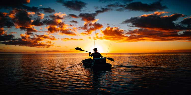 Fisherman on paddling a sit-on-top fishing kayak on the ocean into the sunset.