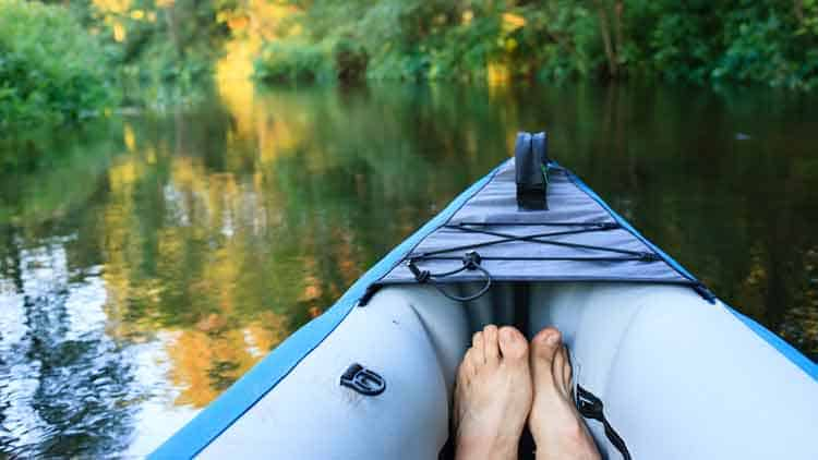 Paddler relaxing in an inflatable kayak on a lazy river.