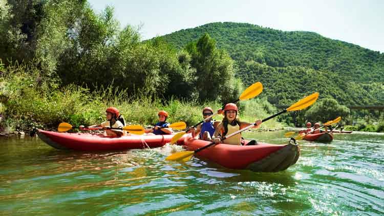 Kayakers paddling inflatable kayaks on a river.